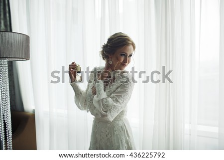 Bride in dress with lace flowers uses a parfume - stock photo