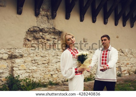 Bride in ethnic dress stands thoughtful behind an old wall while groom goes to her