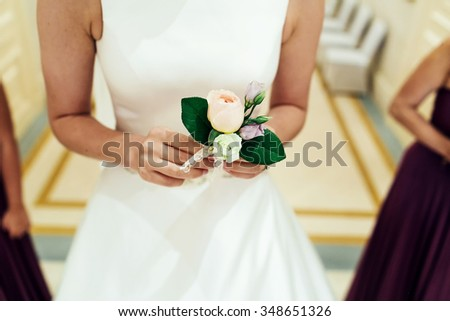 Bride in luxury white wedding dress surrounded by bridesmaids carries to groom delicate boutonniere with roses and leaves. - stock photo