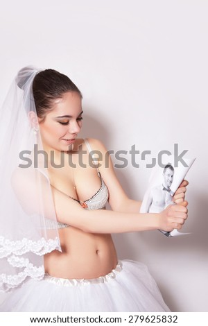 Bride in veil and skirt break the groom photo, studio, gray background - stock photo
