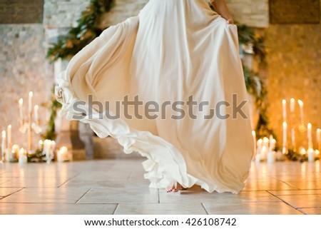 bride in wedding dress dance near candles - stock photo