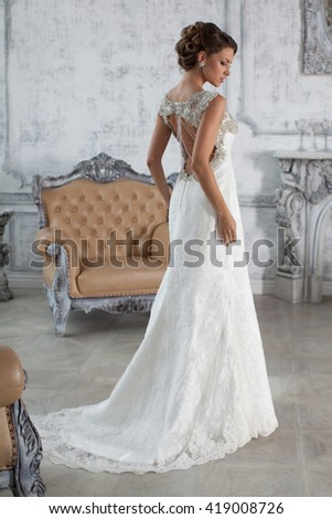 Bride in wedding dress in his apartment in Paris. Wedding photo session in the palace. The girl in a wedding dress in luxurious suites - stock photo