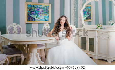 Bride in wedding dress sitting at a table in a luxurious room. - stock photo