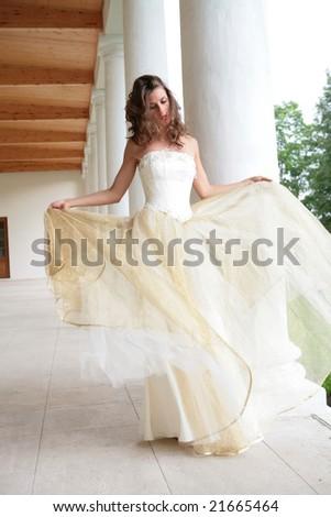 bride in white-golden gown dances amongst pillars - stock photo