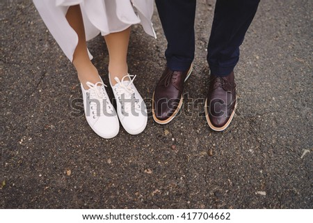 bride in white gumshoes and groom in vinous shoes stand side by side - stock photo