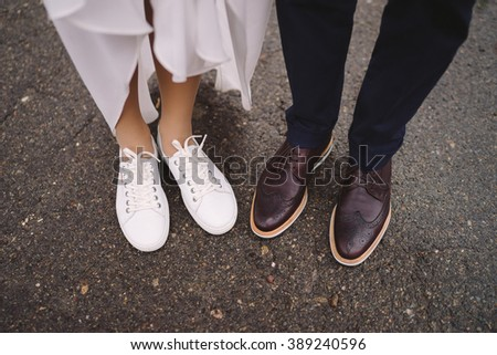 bride in white sport shoes and groom in vinous shoes stand side by side - stock photo