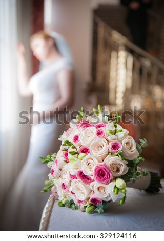 Bride in window frame and wedding bouquet in the foreground. Wedding bouquet with a woman in wedding dress in the background. Beautiful bouquet of white and pink rose flowers. Elegant wedding bouquet  - stock photo