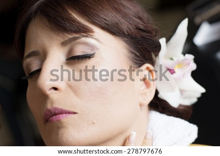 Bride is getting professional make up for her wedding day,almost done. - stock photo