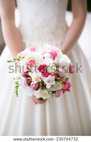 Bride is holding a beautiful delicate pink bridal bouquet - stock photo