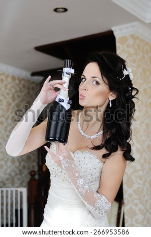 Bride is holding a bottle of champagne as a bridegroom