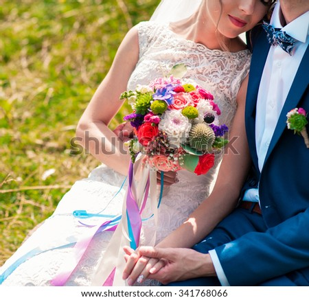 Bride is holding a wedding bouquet  of flowers in a rustic style. Wedding couple - stock photo