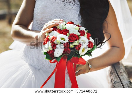 Bride is holding beautiful bright wedding bouquet. bride holding a bouquet - stock photo
