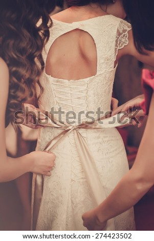 Bride is putting on her white wedding dress - stock photo