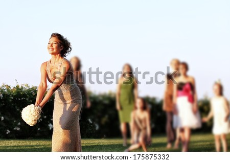 Bride is ready to throw away her wedding bouquet - stock photo
