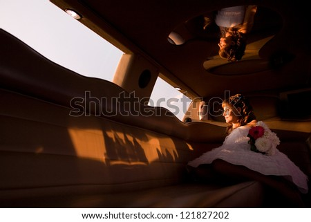 Bride is sitting in limousine  and looking at setting sun