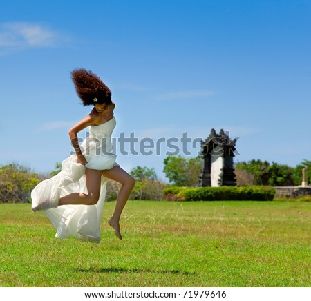 Bride jumped up on a sunny day on the green grass - stock photo