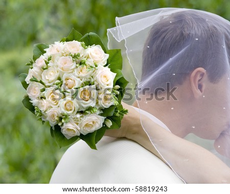 Bride kiss bridegroom, keeping flowers behing him - stock photo