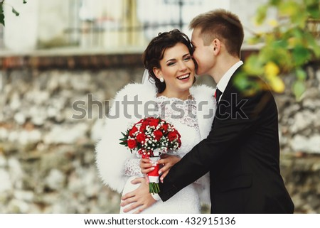 Bride laugh while groom tells her something on the ear - stock photo