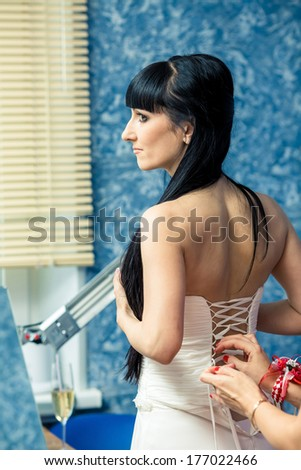 Bride looking at the camera, in a wedding dress laces. - stock photo