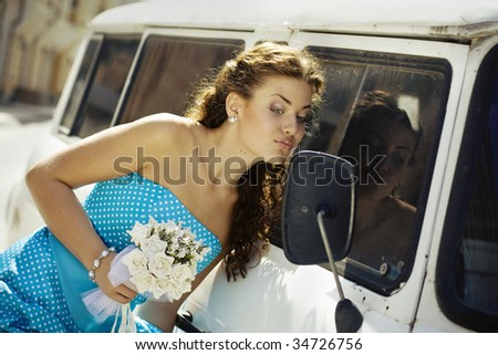 Bride looking in a mirror of old car. - stock photo