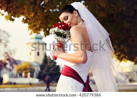 Bride looks misterious holding a wedding bouquet - stock photo