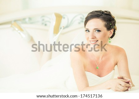 Bride lying on the snow-white bed. - stock photo