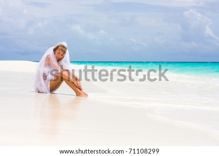 Bride on a coastline at tropical beach - stock photo