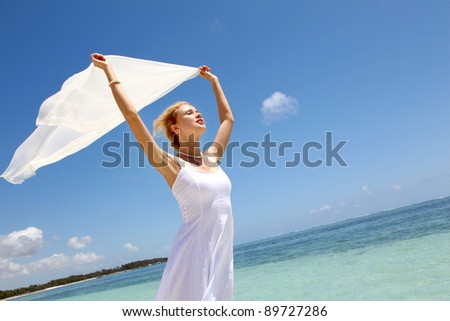 Bride on the beach with white stole - stock photo