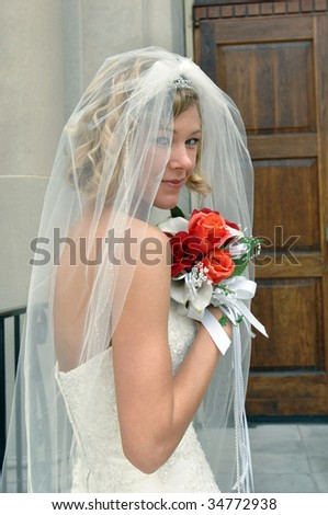 Bride peeks between the folds of her veil as she waits outside the church doors.  She is holding her bouquet of red and orange roses up to her face. - stock photo