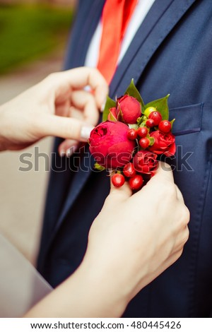 Bride pins a boutonniere made of red flower and berry to blue jacket
