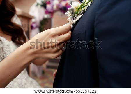 Bride pins beige boutonniere to groom's blue jacket