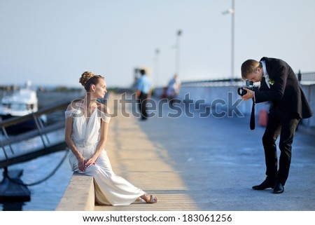 Bride posing for her groom while shooting with an old camera - stock photo