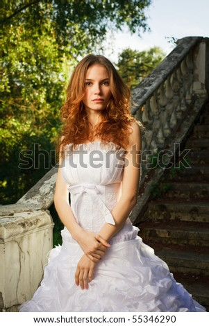 Bride posing on stairs of old abandoned house - stock photo