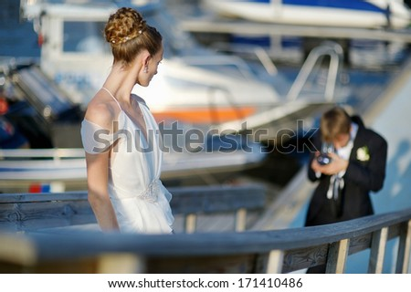 Bride posing while her groom is shooting with an old camera - stock photo