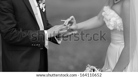 Bride puts a ring on finger of her groom. Picture in black and white. Togetherness. - stock photo
