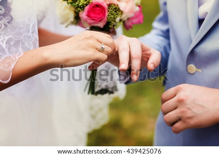 Bride puts a ring on groom's finger - stock photo