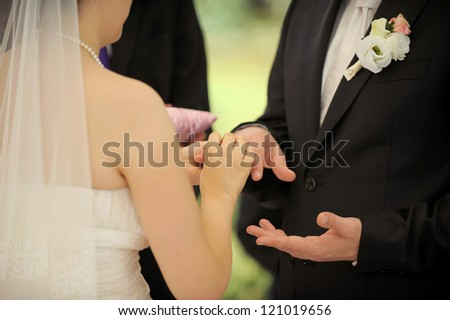 bride puts wedding ring on groom's finger - stock photo