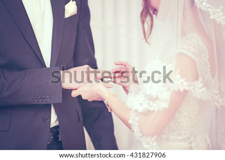 Bride putting a ring on groom's finger - stock photo