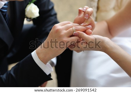 Bride putting a wedding ring on a groom's finger - stock photo