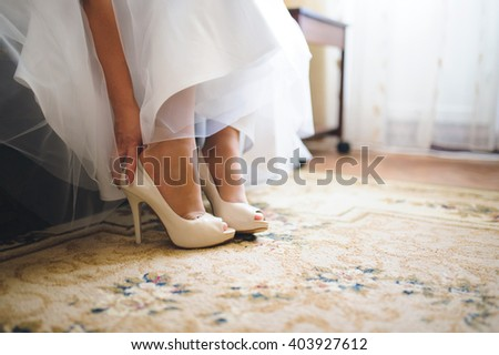 bride putting on wedding shoes at home