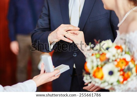 Bride putting the ring on groom's finger on the wedding ceremony - stock photo