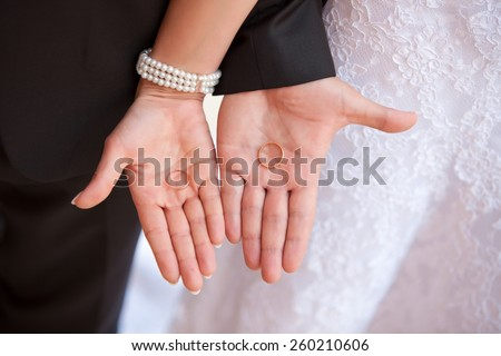 Bride's and groom's hand with wedding rings on the palms - stock photo
