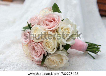 Bride's beautiful pink and white bouquet of roses displayed on a white lace wedding dress