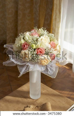 Bride's bouquet of pink and white roses on the corner of table in  the restaurant close up - stock photo