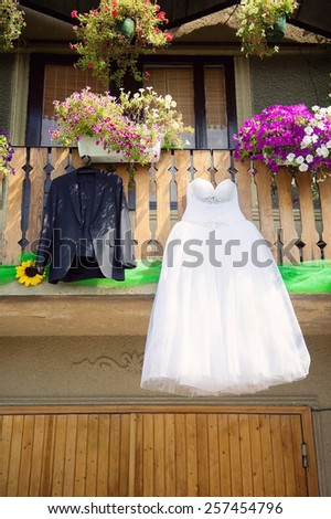 bride's dress and groom's suit hanging in yard - stock photo