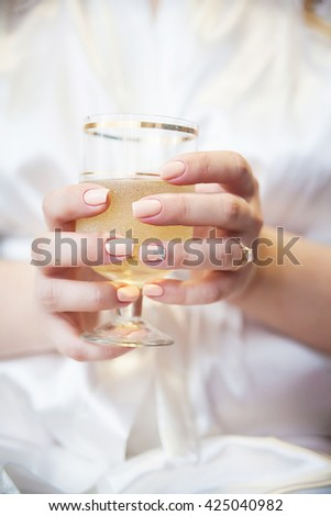 Bride's hand with a wedding ring holding a glass of champagne with bubbles.