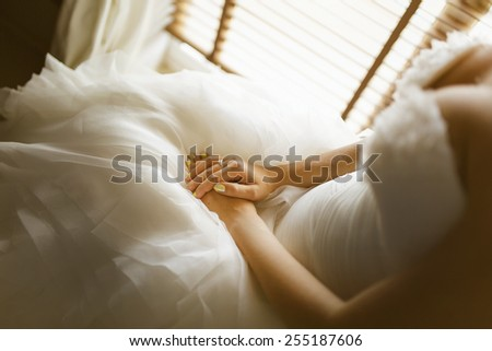 bride's Hand with ring on white dress - stock photo