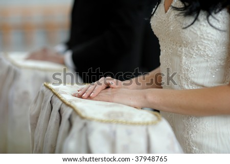 Bride's hands on the pillow during wedding church ceremony