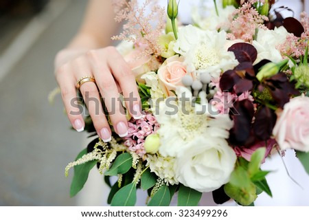 Bride's hands with a wedding ring on a finger and wedding flowers