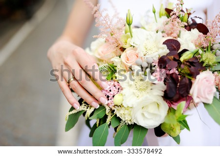 Bride's hands with a wedding ring on a finger and wedding flowers - stock photo